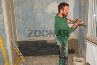 Man pushes ornament tiles to a wall