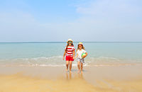 Happy sisters playing in sand on a beautiful beach