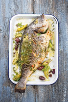 Fresh Greek barbecue gilthead seabream with peperoni and Kalamata olives as top view in a white skillet