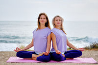 Women sit in lotus pose do yoga exercise meditating on beach near sea