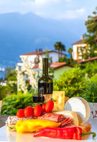 Still life with wine and Italian delicacies