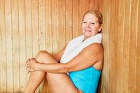 Senior Frau sitzt entspannt in der Sauna