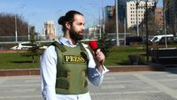 Reporter with a microphone wearing a vest