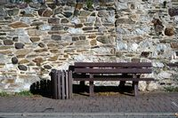 Park bench in front of field stone wall