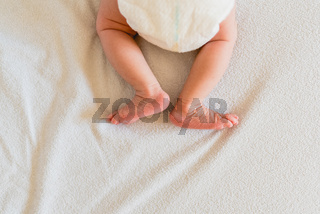 Small legs and feet of newborn baby on his bed.