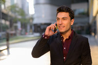 Happy young Hispanic businessman thinking while talking on the phone outdoors