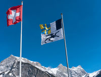 flags of Switzerland and the Grisons canton blowing in the wind in a blue sky in the mountains