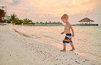 Three year old toddler boy on beach at sunset