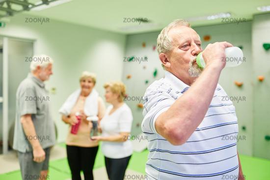 Durstiger Senior trinkt Wasser aus einer Flasche