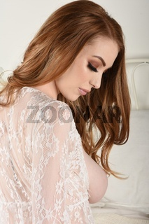 Schone, vollbusige Rothaarige in einem Spitzenkleid, auf ihrem Bett, Oben Ohne