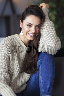 Portrait of a young happy beautiful woman in warm clothings at home