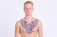 Young handsome shirtless man with blond hair and tattoo on body
