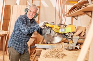 Handwerker mit Gehörschutz an der Kappsäge