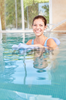 Junge Frau schwimmt entspannt im Pool