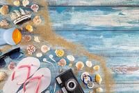 Beach accessories retro film camera sunglasses flip flop and sea shell on wood