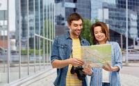 couple of tourists with map and camera in city
