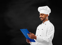 chef reading menu on clipboard over chalkboard