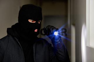 Einbrecher oder Dieb nachts mit Taschenlampe