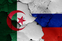 flags of Algeria and Russia painted on cracked wall