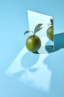 Lime with green leaves and a mirror on a blue background with shadows and a copy of a spacer. Creative food composition