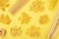 Italian pasta variety, shot from above on a yellow background, a flat lay banner