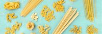A panorama of Italian pasta variety, flat lay banner, overhead shot on a blue background