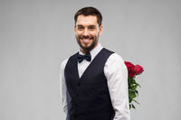 happy man with red roses behind his back