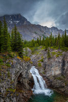 A small waterfall in the Canadian Rocky Mountains on a grey rainy day