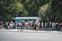 Many people standing in queue  on street at tourist attraction (German Reichstag) on summer day in Berlin, Germany