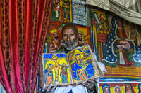 priest of the rock-hewn church Mikael Mellehayzengi showing the book Miracles of Maria, Ethiopia
