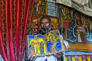 Orthodoxer Priester der Felsenkirche Mikael Mellehayzengi zeigt das Buch Wunder der Maria mit frabenfrohen handgemalten Abbildungen auf Pergament