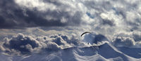 Evening mountain with clouds and silhouette of parachutist