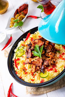 Tajin with couscous, vegetables and meat on white background