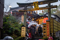 KYOTO, JAPAN - 10 FEB 2018: Low shot of a staircase with yellow signs in Kiyomizu Dera Temple with people walking and wearing umbrellas