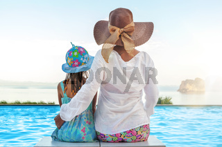 Mother and daugher sitting at infinity pool.