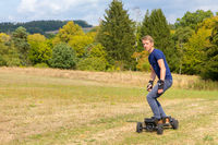 european teenage boy rides electric mountainboard in nature