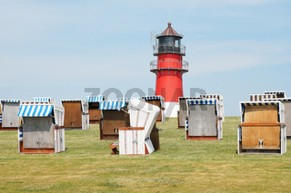 dike with hooded beach chairs and lighthouse