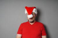 christmas hater hiding face behind santa hat