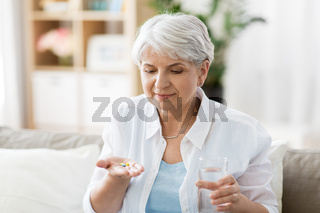 senior woman with water taking medicine at home