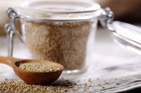 Raw organic superfood gluten free quinoa seeds in wooden spoon and glass airtight jar on kitchen table closeup