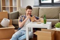 smiling man eating takeaway food at new home