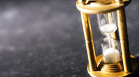 Concept timekeeping. Sand trickles through an hourglass