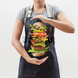 Big homemade fresh burger in the girl's hands from flying ingredients - fresh vegetables and organic natural beef meat on a white background.