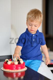 Boy trying birthday cake