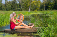 Young woman sits with mirror at water in nature