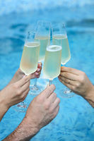 People hold champagne glasses in the pool