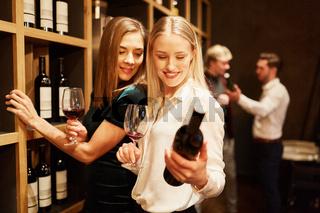 Zwei junge Frauen schauen auf eine Flasche Rotwein