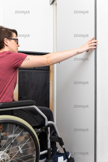 disabled woman opens a door in her flat