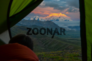 Sunrise view of Mount Denali (mt Mckinley) peak with red alpenglow directly from camping tent from Stony Dome overlook. Denali National Park and Preserve, Alaska, United States