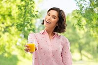 happy young woman in pajama holding orange juice